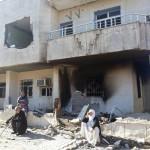 Familie vor zerstörtem Haus in Hezex